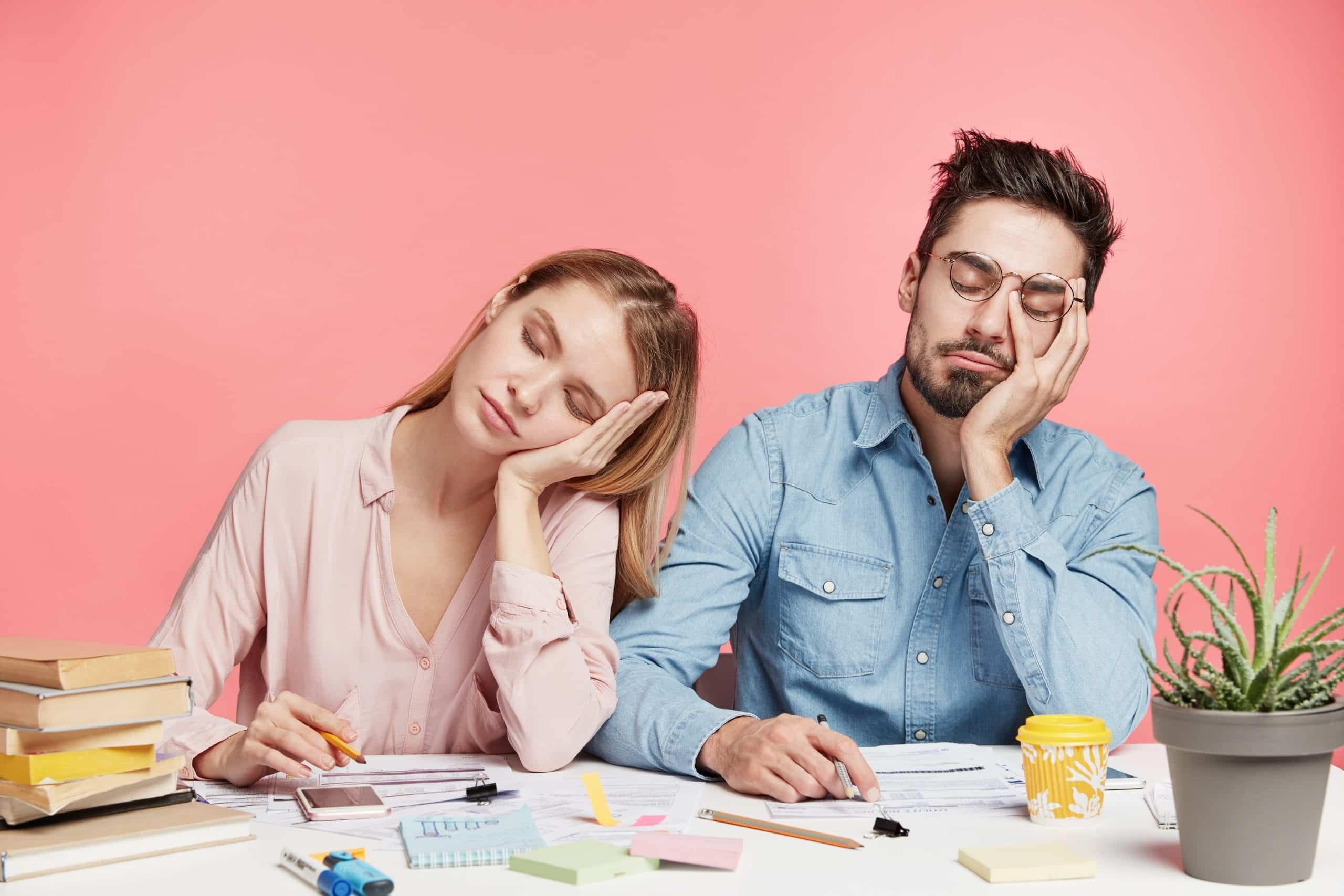 Portrait tired crew of office workers sit at table, fall asleep after working long hours on preparing startup project, feel tiredness, isolated over pink background. People and overworking concept