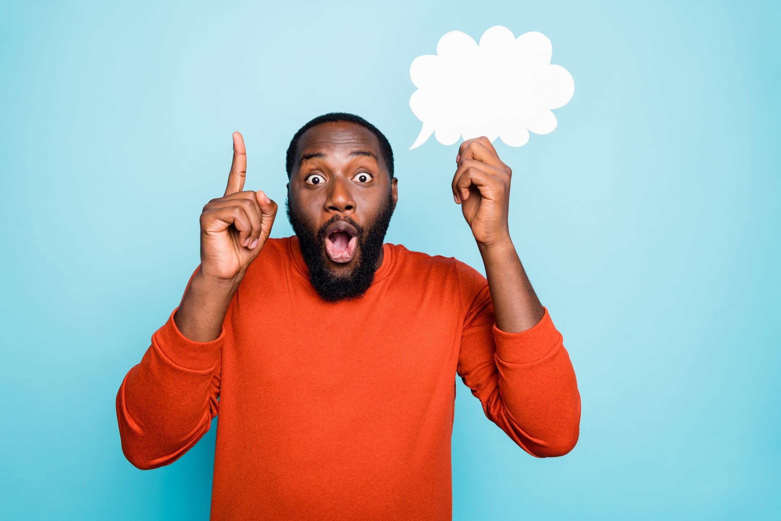 Photo of funny cheerful mixed-race man showing his forefinger up with amazement on face holding white bubble of thoughts isolated, vivid blue color background